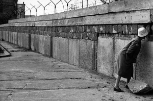 Black and white historical photograph of a woman standing at the Berlin Wall circa 1962 for Flash Fiction: Cold War by Malin James