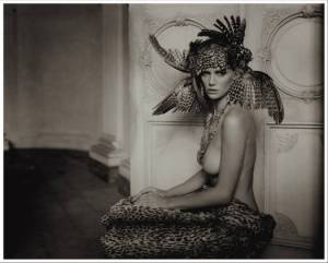 Sepia toned photograph of a nude woman wearing a feathered head dress. For On Reading Sex by Malin James