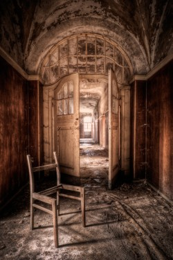 Photograph of a wealthy abandoned house with broken chair in the foreground, for Memory Palace by Malin James