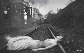 Black and white photograph of a woman in a white dress lying on train tracks, for The Joy of Catharsis by Malin James